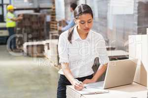 Warehouse manager using laptop and clipboard