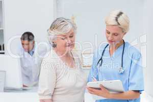 Nurse communicating with patient while doctor using computer