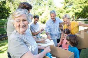 Happy volunteer family separating donations stuffs