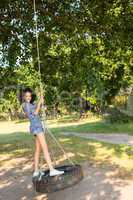 Pretty young woman in tire swing