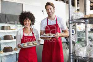 smiling colleagues showing plate of desert