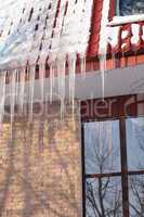 icicles on building roof at winter day