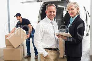 Managers smiling at camera with delivery driver behind