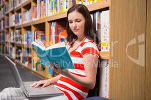 Student sitting on floor in library reading