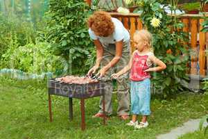 Little girl helping her mother to cook shish kebab