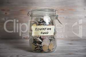 Money jar with education fund label.