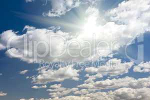 Deep Blue Sky and Puffy Clouds With Sun Rays