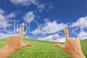 Female Hands Framing Deep Blue Sky Above Grass Field