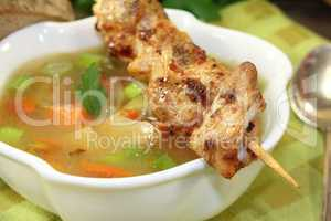 Geflügelconsomme mit Hähnchenspieß und Suppengrün