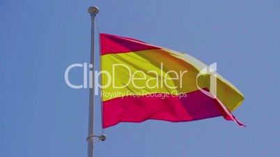 Civil, commercial Spain flag without coat of arms to blue sky, slow motion