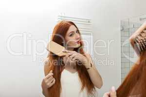 Woman Brushing her Hair In Front a Mirror