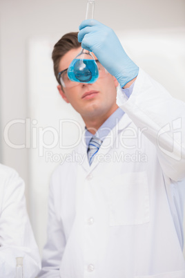 Scientist looking at beaker with blue fluid