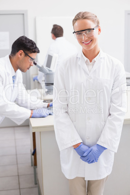 Smiling scientist looking at camera while colleagues working beh