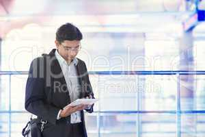 Man using tablet computer at train station