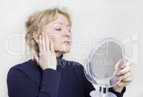 ältere Frau schaut in Spiegel