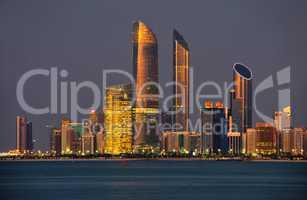 Skyline von Abu Dhabi im Abendlicht mit Wasser im Vordergrund