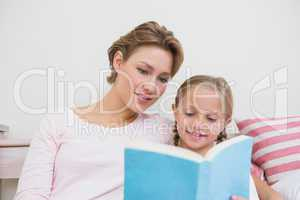 Mother reading her daughter bedtime story