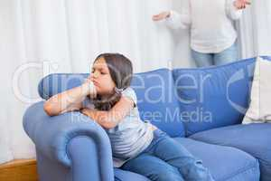 Angry little girl sitting on the couch