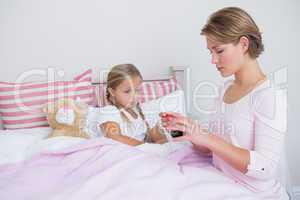 Mother about to give medicine to sick daughter
