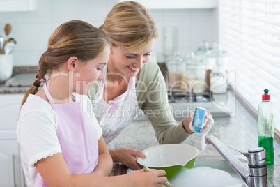 Happy mother and daughter washing up together