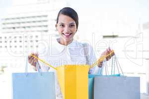 Happy woman looking inside shopping bags
