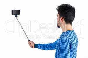 Casual man using a selfie stick