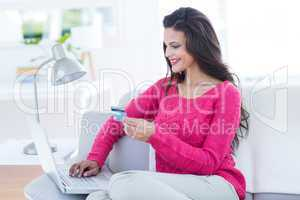 Smiling beautiful brunette doing online shopping on the couch