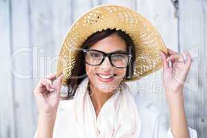 Smiling beautiful brunette wearing straw hat and looking at came
