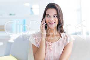 Smiling beautiful brunette relaxing on the couch and speaking on