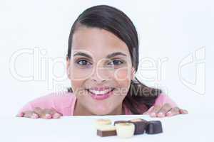 Pretty brunette peeking at chocolate looking at camera