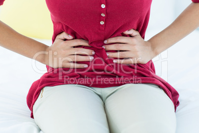 Woman sitting on bed with stomach pain
