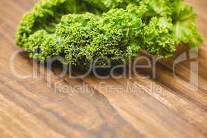 Curly parsley on wooden board