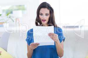 Surprised beautiful brunette reading letter