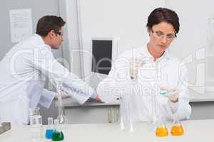 Scientist pouring chemical fluid in funnel and her colleague wor