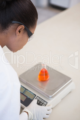 Scientist weighing beaker with orange fluid inside