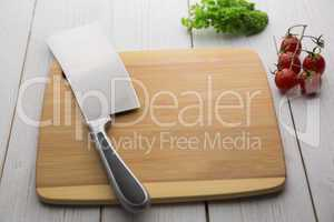 Chopping board with large knife and ingredients