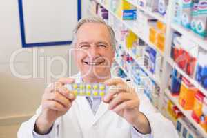 Senior pharmacist holding up blister packs