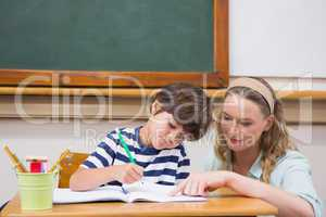 Teacher helping pupil in classroom