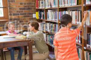 Teacher helping pupil in library