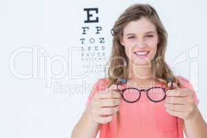 Hipster showing glasses next to an eye test