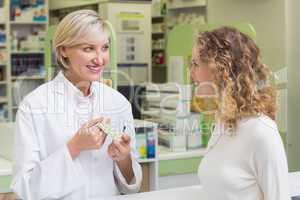 Pharmacist showing blister packs to costumer