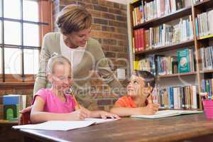 Teacher helping pupils in library