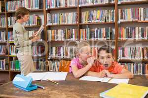 Cute pupils speaking at library