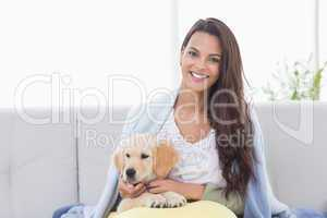 Portrait of woman playing with puppy