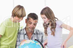 Siblings with father exploring map on globe