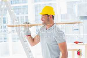 Handyman carrying planks in building