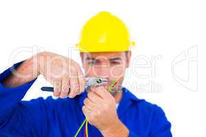 Electrician wearing hard hat while cutting wire with pliers