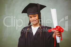 Little girl in graduation robe holding diploma