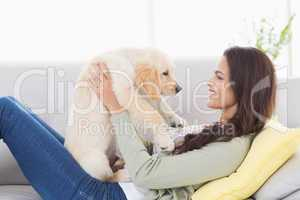 Woman playing with puppy on sofa