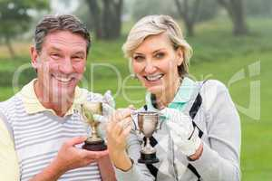 Happy golfing couple with trophy
